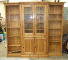 A modern pine breakfront bookcase/cabinet, having a pair of central glazed doors and cupboard doors,