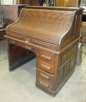 A small oak roll-top desk, the tambour front enclosing an arrangement of pigeon holes and small