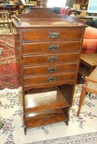 An Edwardian stained wood music cabinet of five drop-down doors above two shelves, 50cm wide,