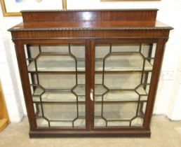 An early-20th century mahogany display cabinet, the rectangular top above a pair of astragal-