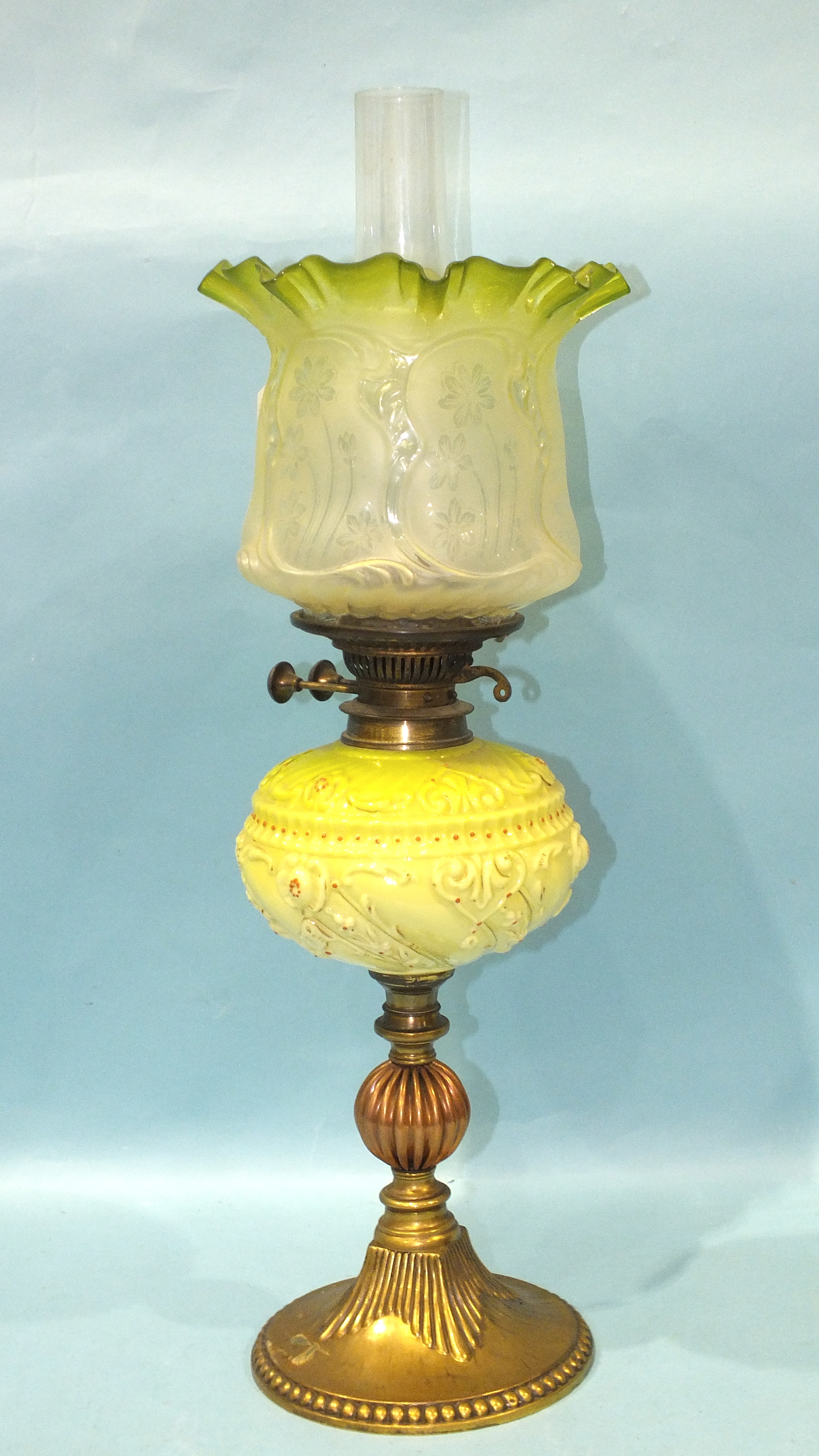 A Victorian brass and copper oil lamp with moulded pale green glass reservoir and etched glass