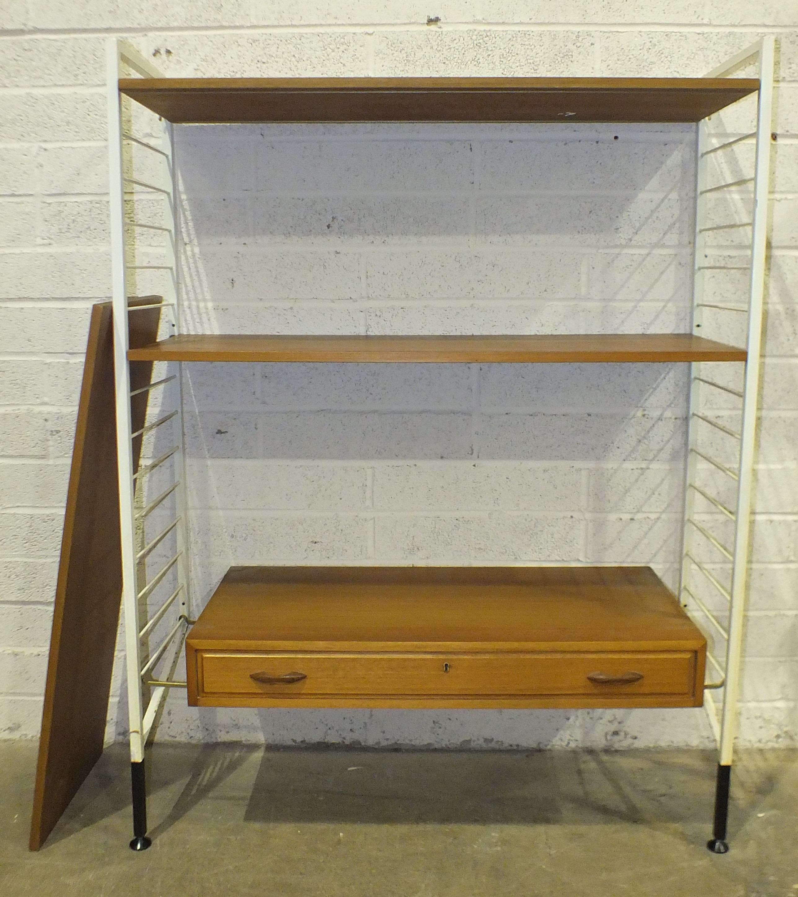 A Ladderax shelf unit, the white metal supports with drawer and three shelves, 90cm wide, 144cm