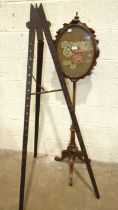 A Victorian walnut pole screen with oval needlework panel, 37 x 47cm, on tripod support 150cm high