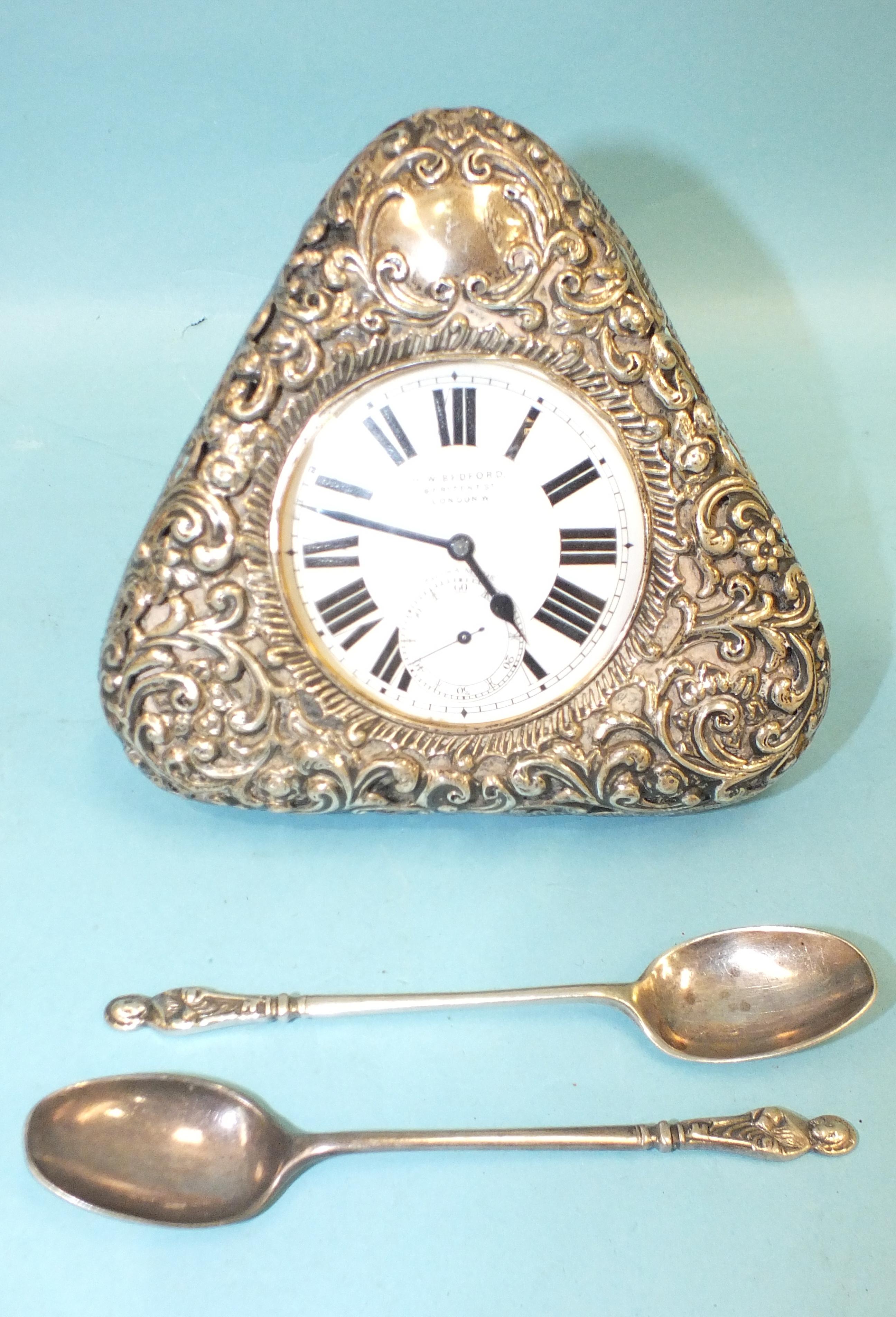 A silver embossed pocket watch holder of triangular form, Birmingham 1898, 11.5 x 11.5cm, (holes