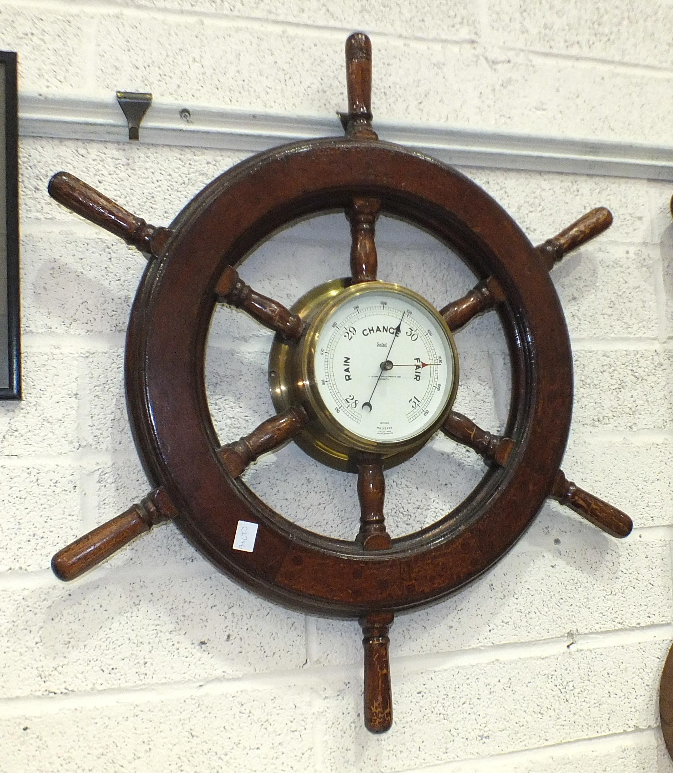 A Sestrel brass bulkhead barometer, 19cm diameter, set within a wooden ship's wheel, 71cm overall.