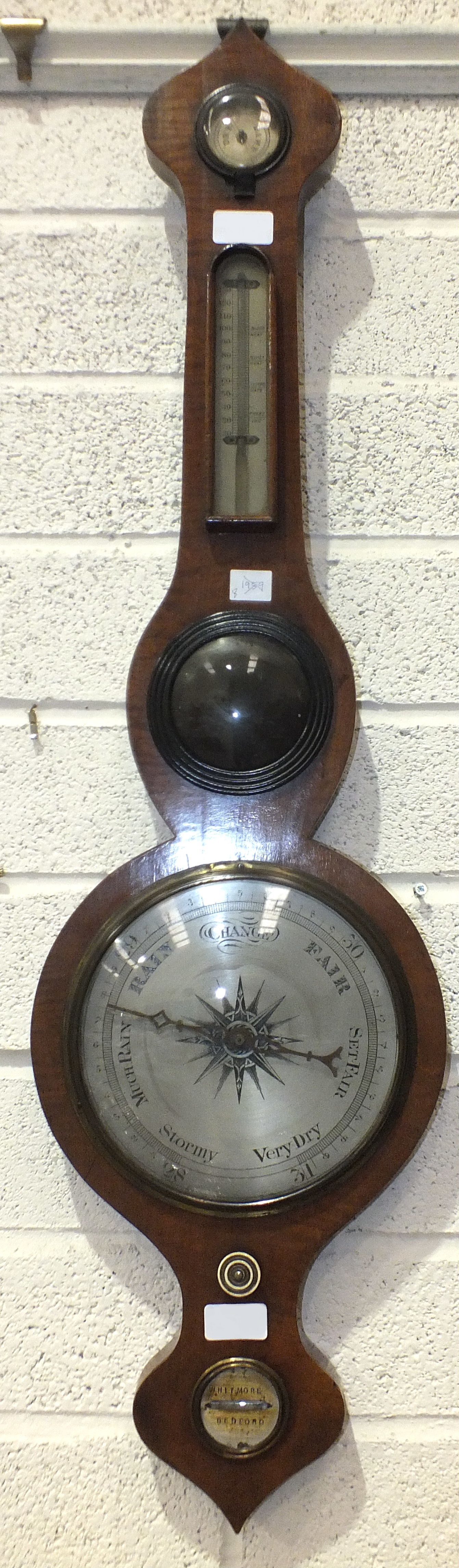 A mahogany wheel barometer with silvered dry/damp thermometer and barometer dials, the spirit