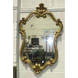 A modern gilt scrolling frame wall mirror, 98 x 63cm, a wool-work picture and an oleograph