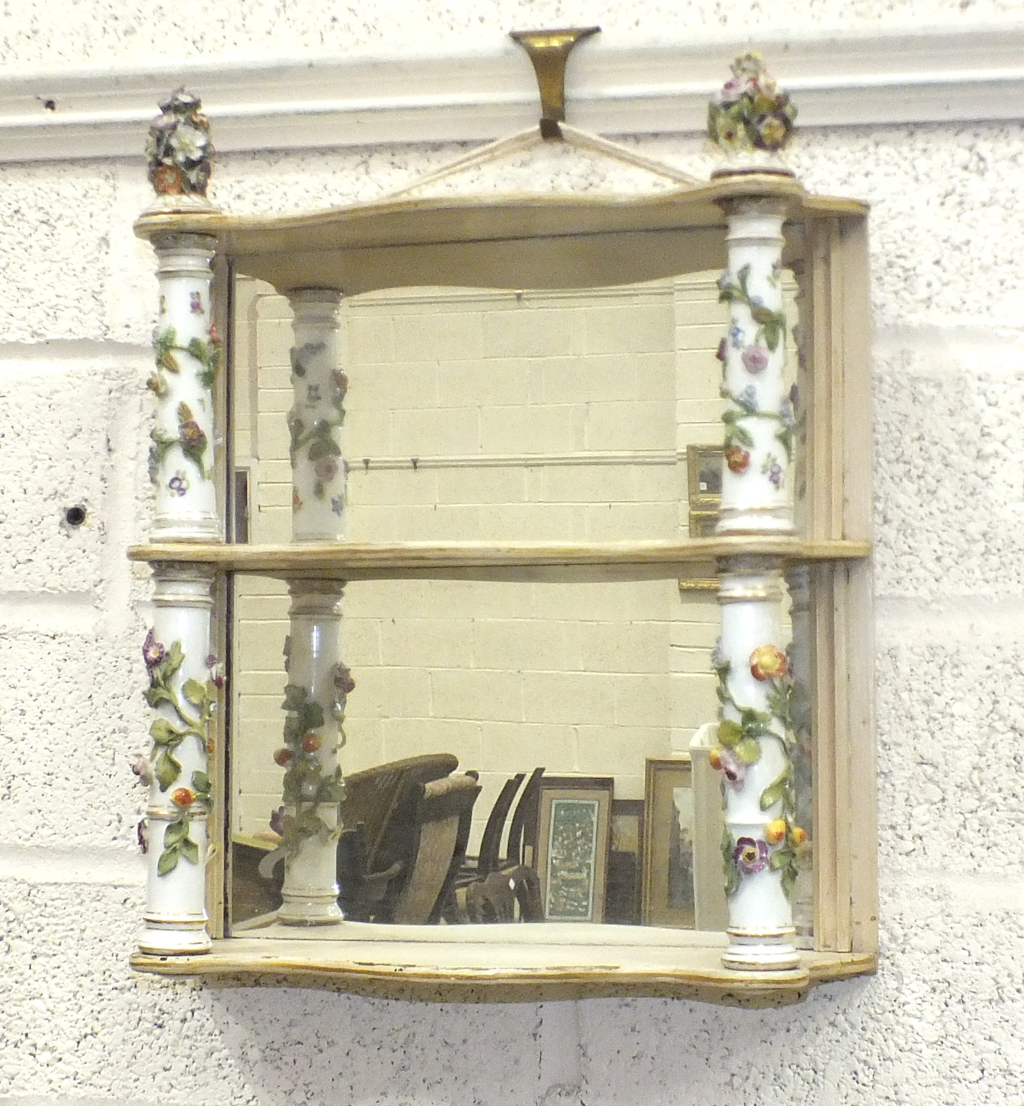 A Continental painted wood three-tier mirrored-back wall shelf, the shelves separated by floral-