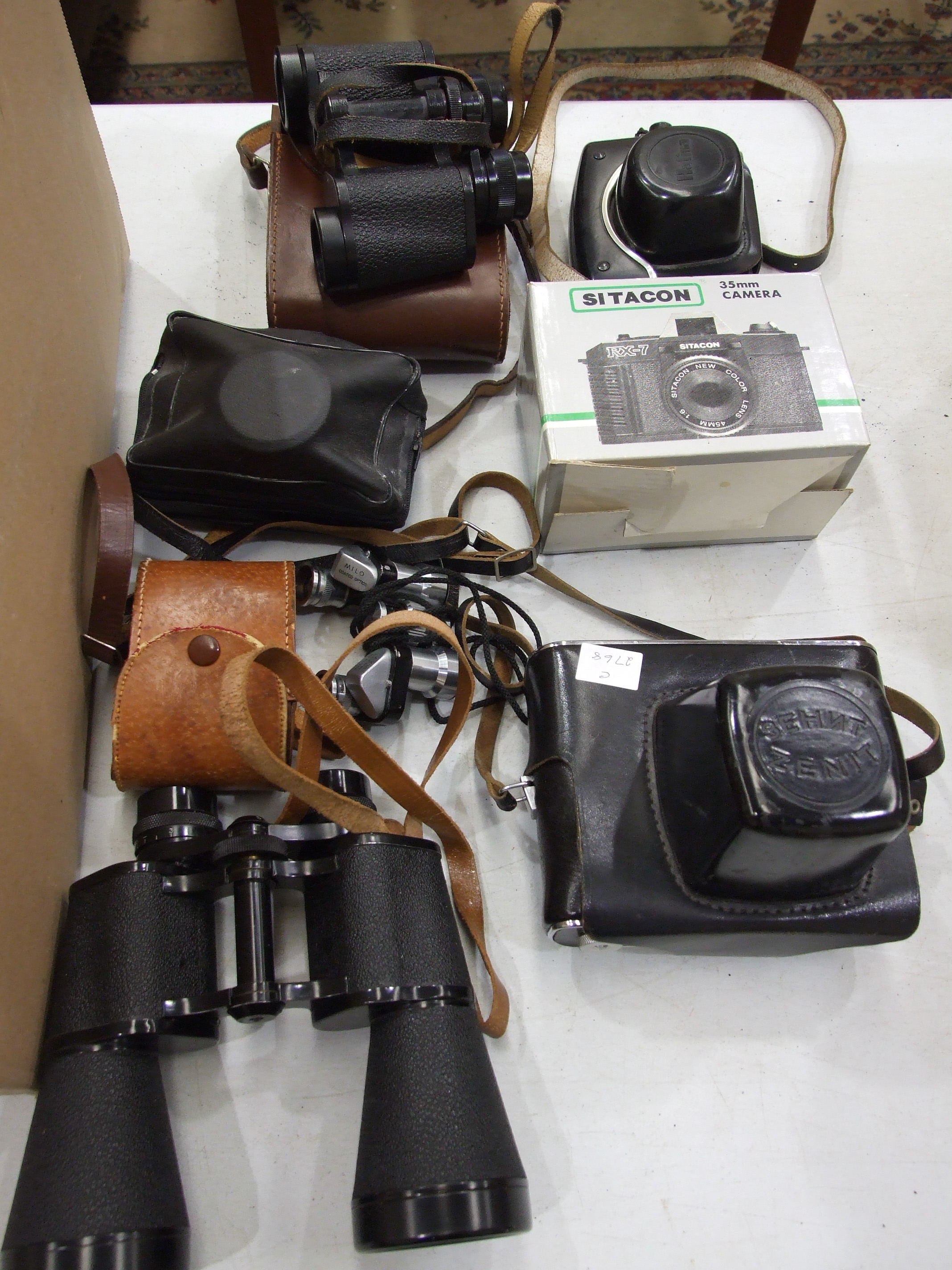 A Zenit-E 35mm camera in case, a Halina camera, other cameras, a pair of Milo 7 x 18 field glasses