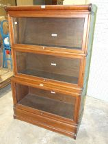 A Globe Wernicke mahogany three-tier bookcase, with glazed up-and-over doors, (one unglazed), on