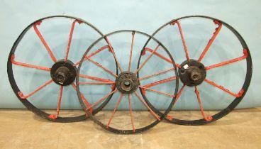 A pair of iron spoked cart wheels, 72cm diameter and a smaller iron spoked wheel, 63cm diameter, (