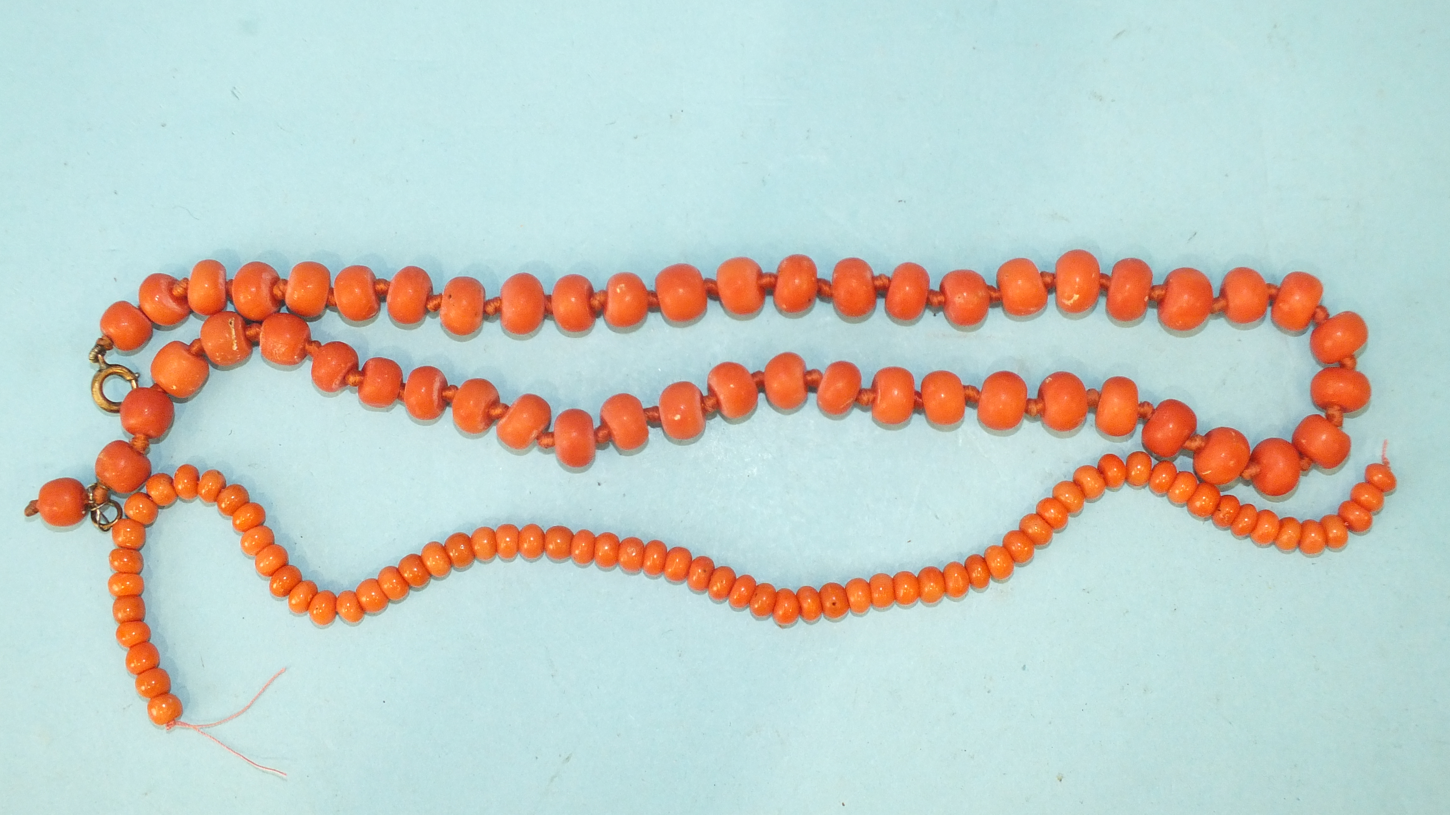 A necklace of fifty-one coral beads, 8-9mm diameter approximately, 45cm long, 45g and a string of