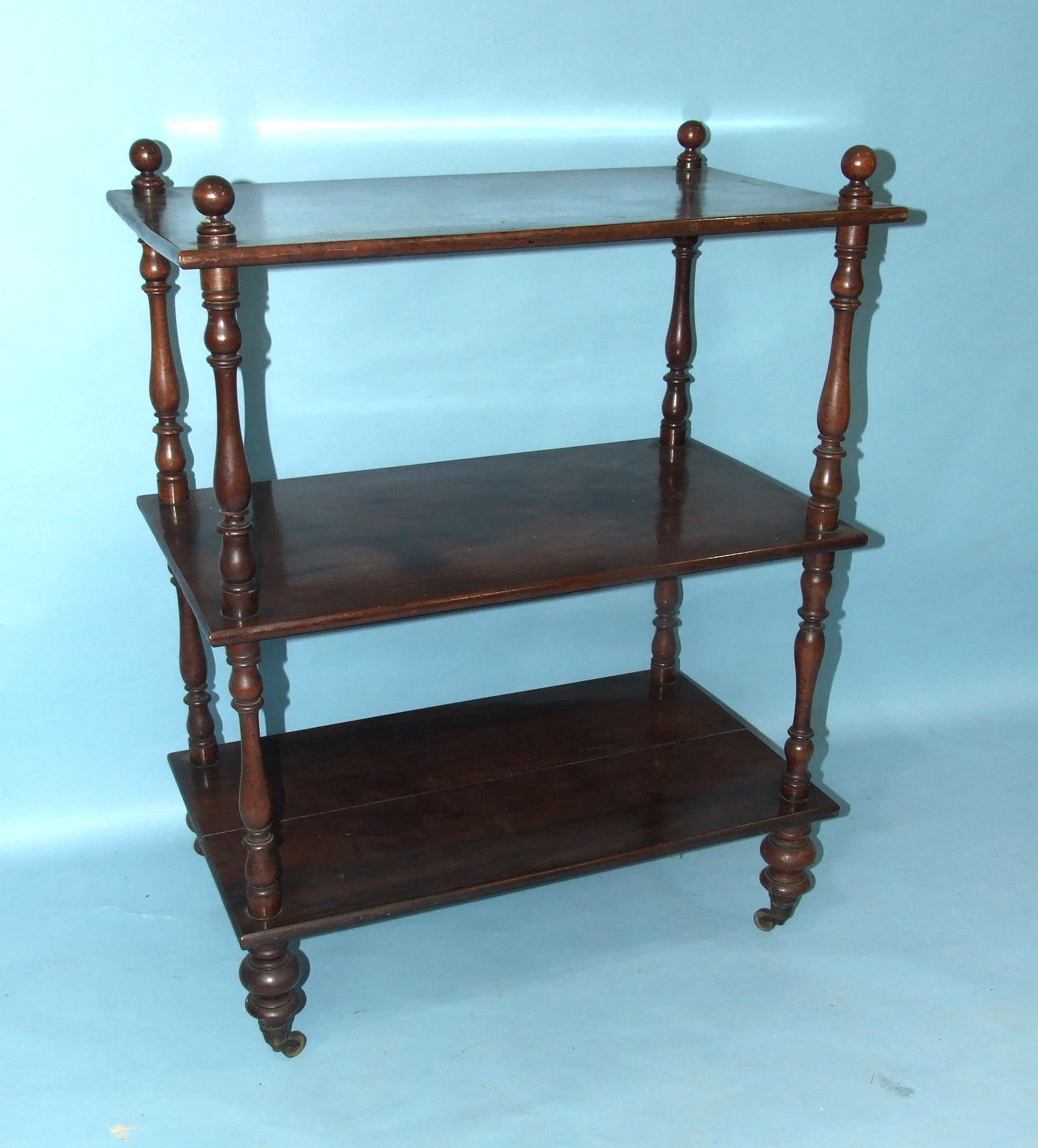 A Victorian mahogany three-tier whatnot on turned legs with castors, 73cm wide, 96cm high, a