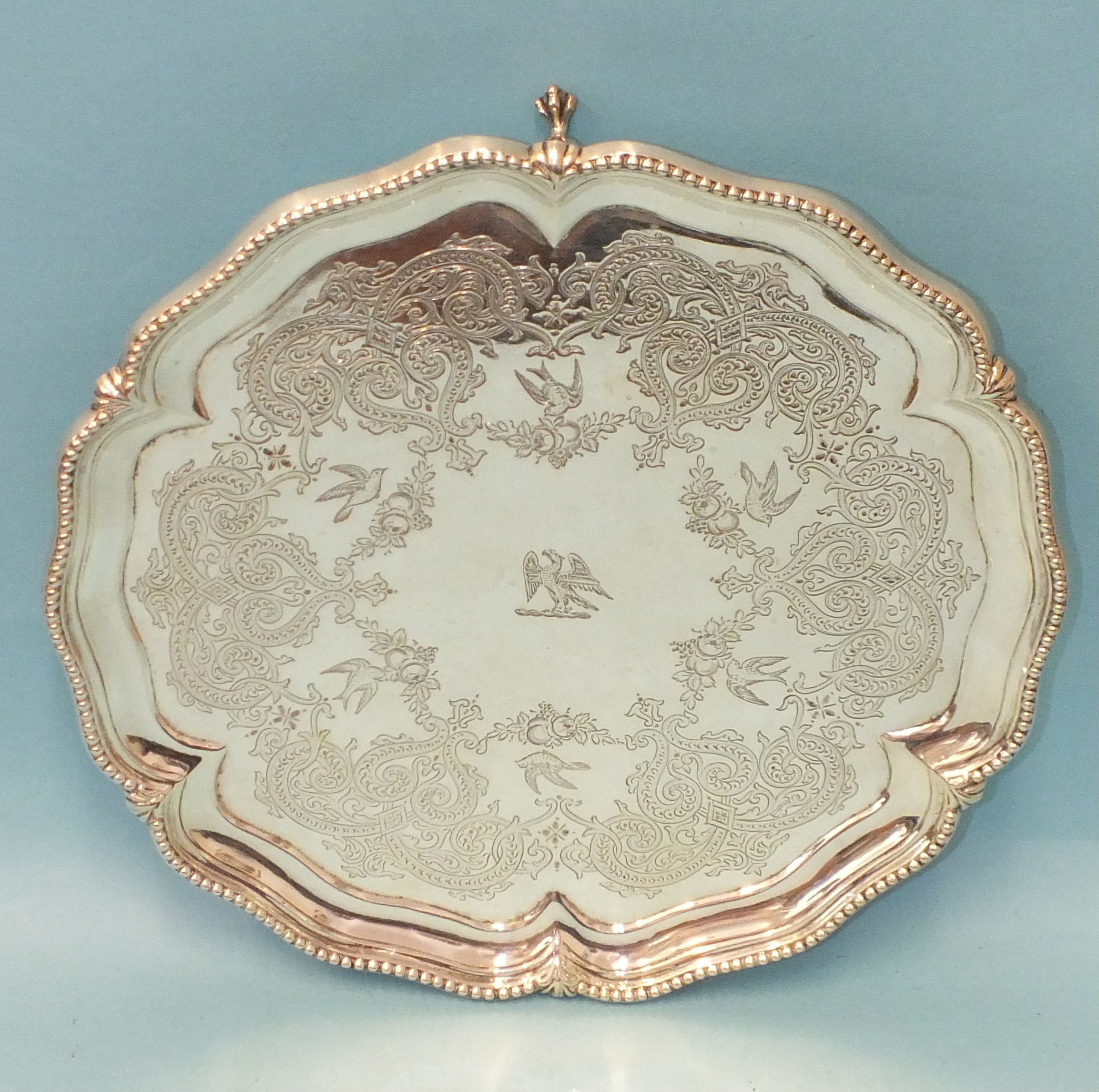 A Victorian silver salver of shaped circular form, with beaded rim and engraved decoration, raised