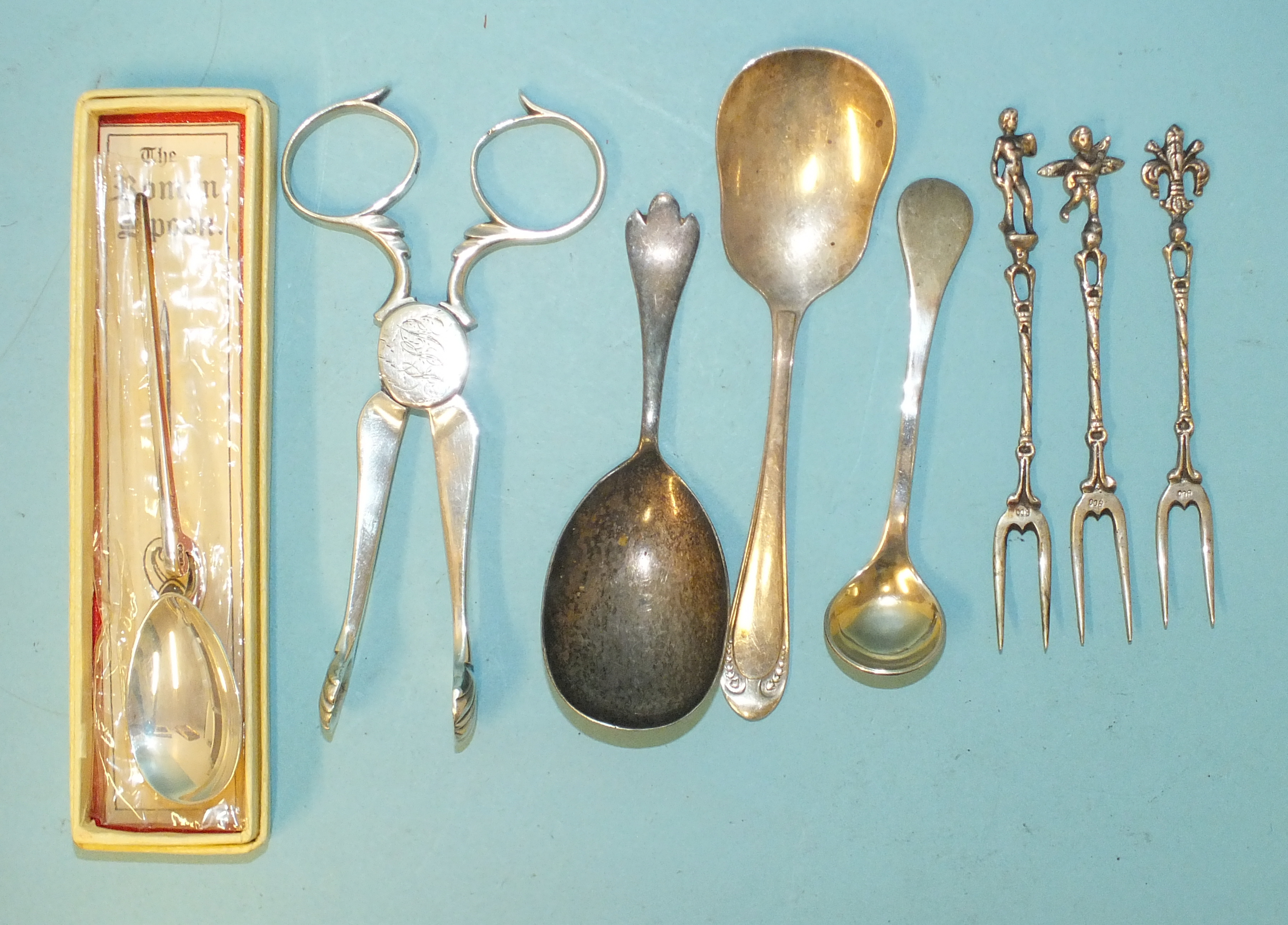 A pair of 18th century silver sugar nips with engraved initials, a reproduction Roman spoon,