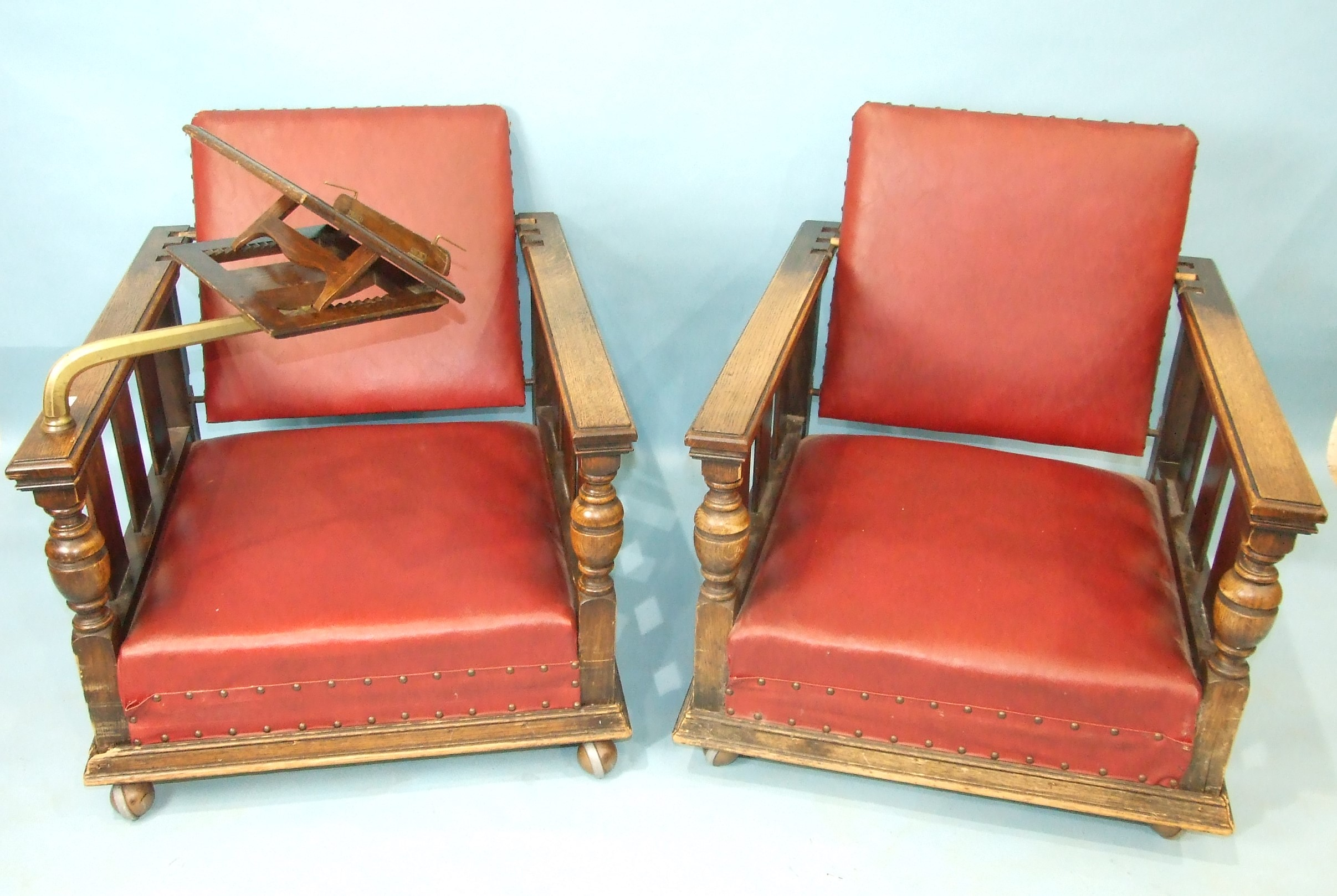 A pair of 1930's oak deep-seated armchairs with adjustable backs, on later castors, one with