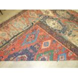 An antique Oriental carpet having four central blue ground lozenges and overall hooked medallions,