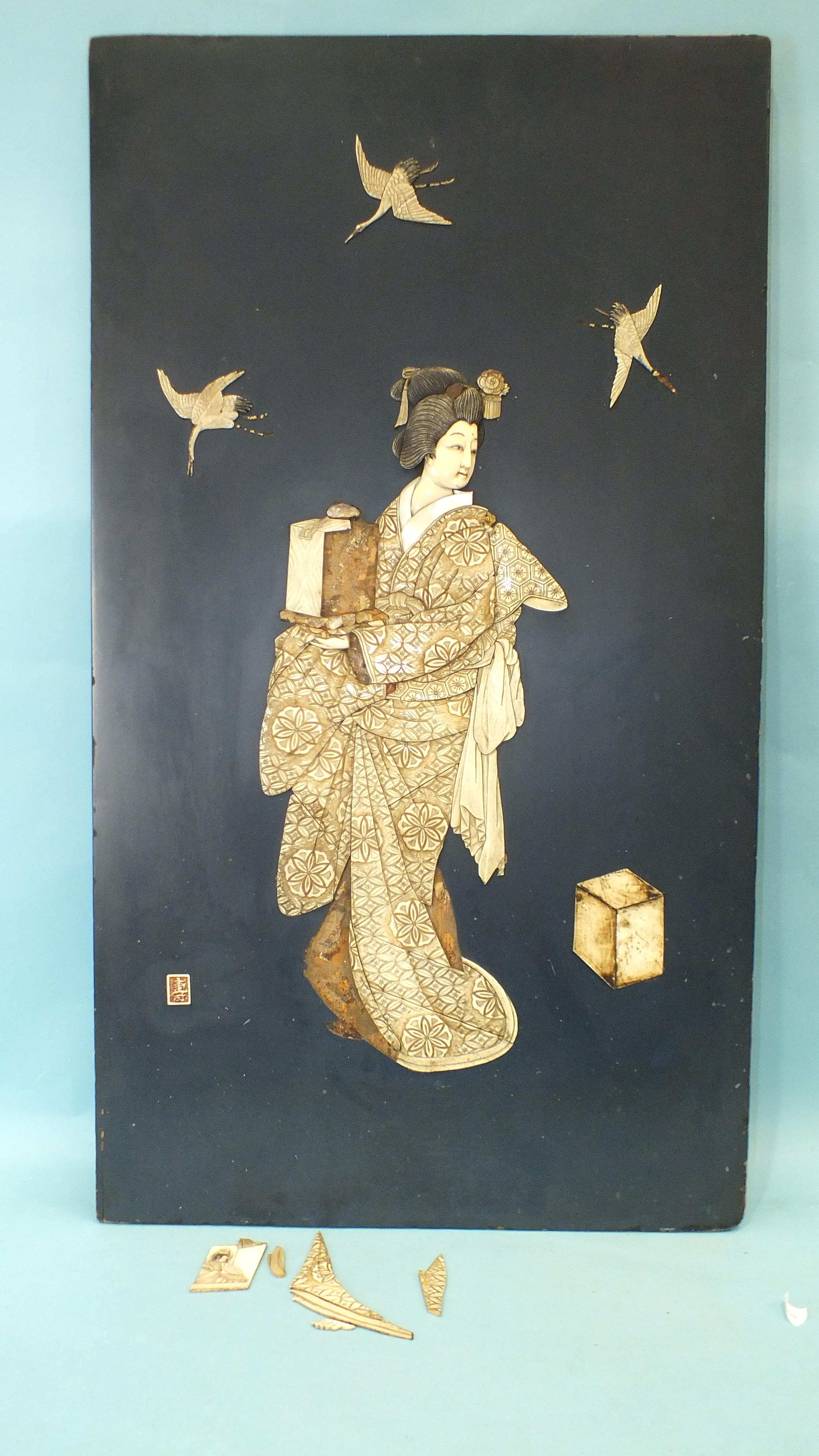 An early-20th century Japanese lacquered panel with applied carved ivory, bone and mother-of-pearl