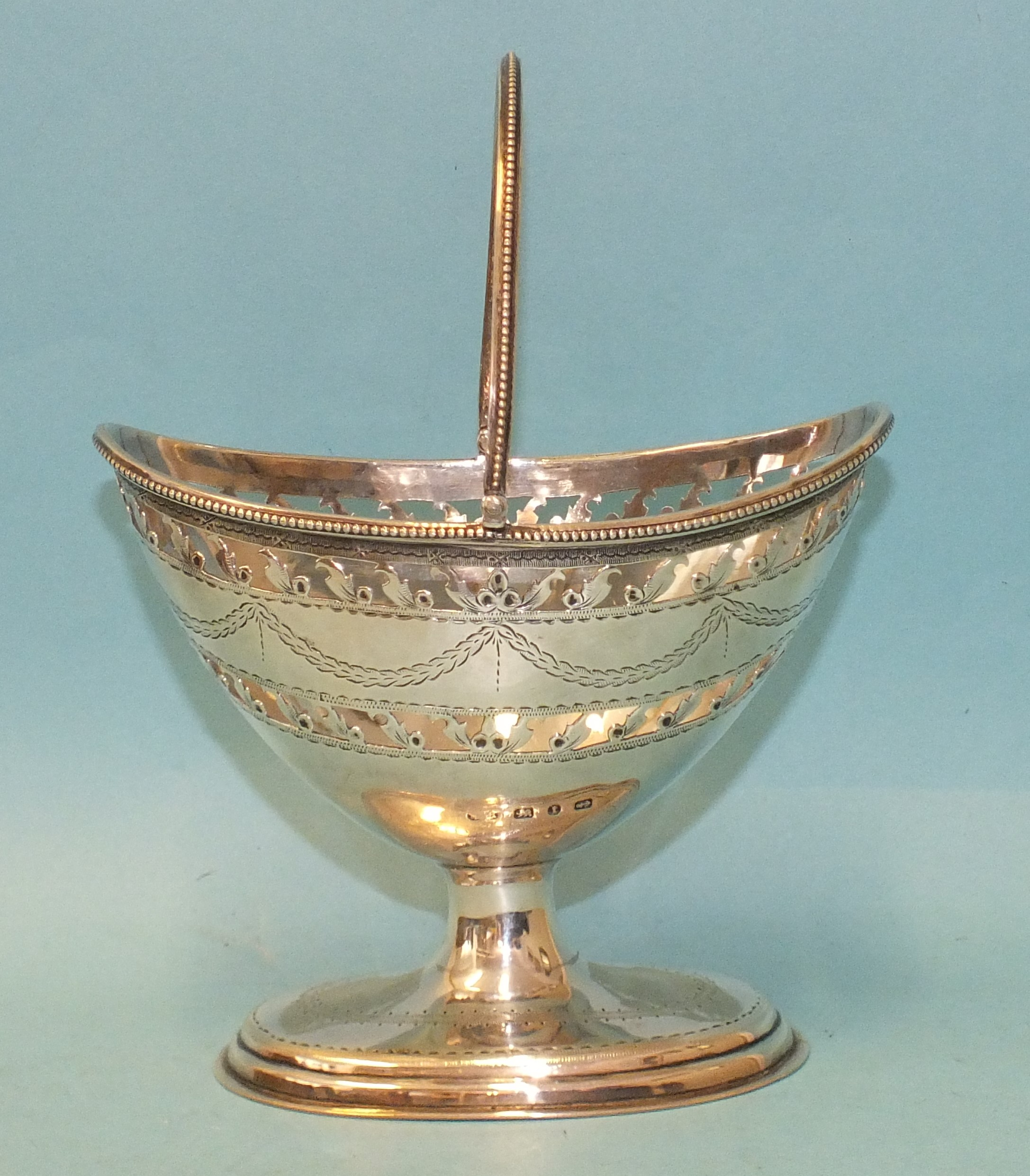 A Victorian silver helmet-shaped swing handle sugar basket with beaded border, engraved decoration