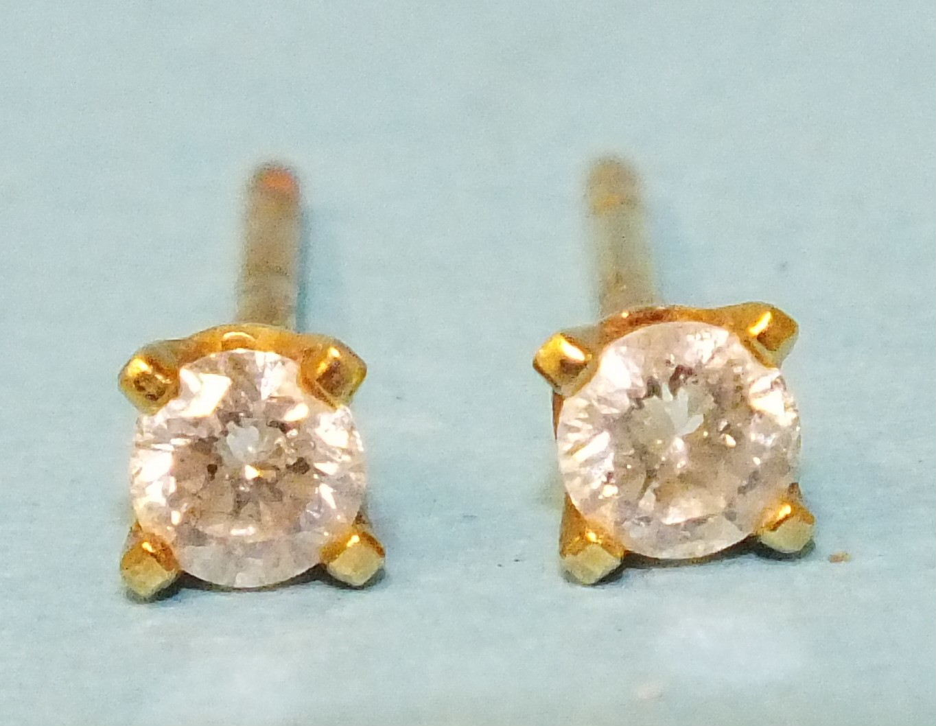 A pair of diamond stud earrings, each claw-set a brilliant-cut diamond of approximately 0.14cts,