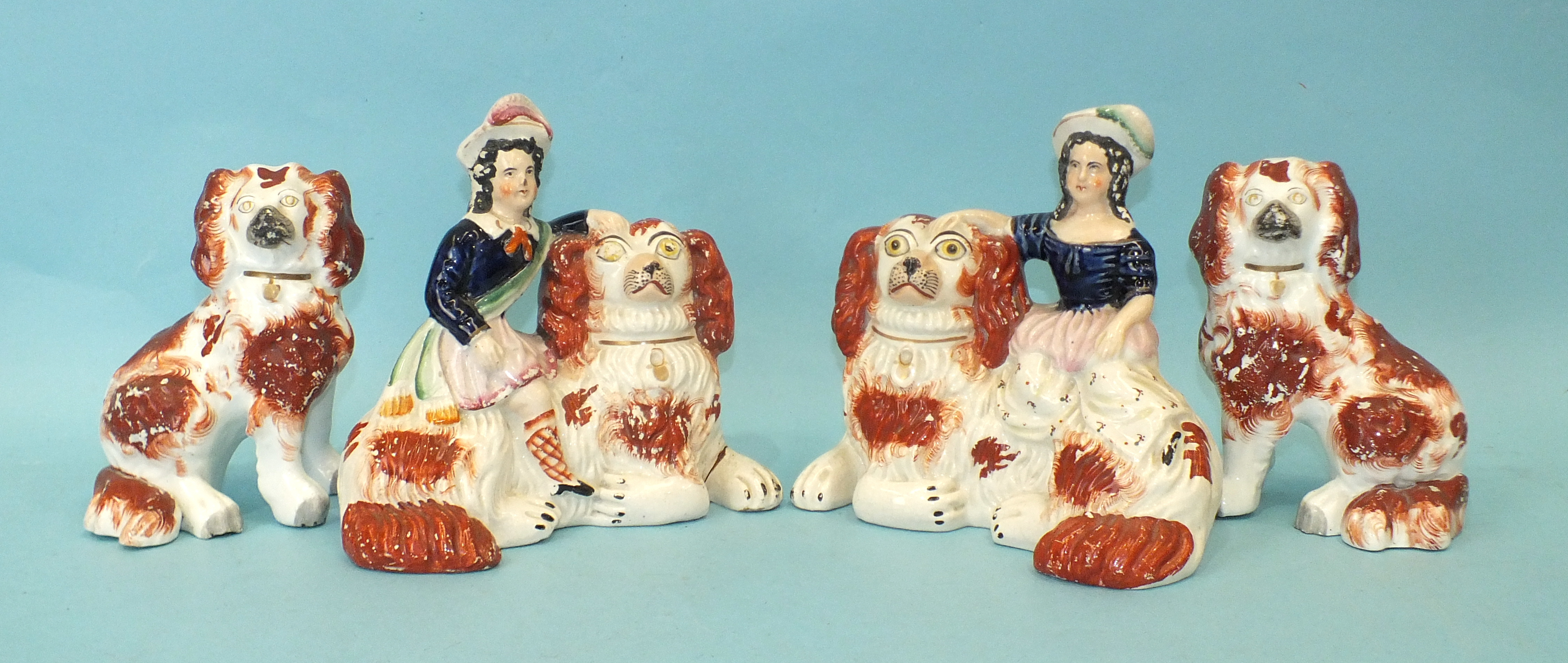 A pair of 19th century Staffordshire recumbent liver and white spaniels, with a figure of a young