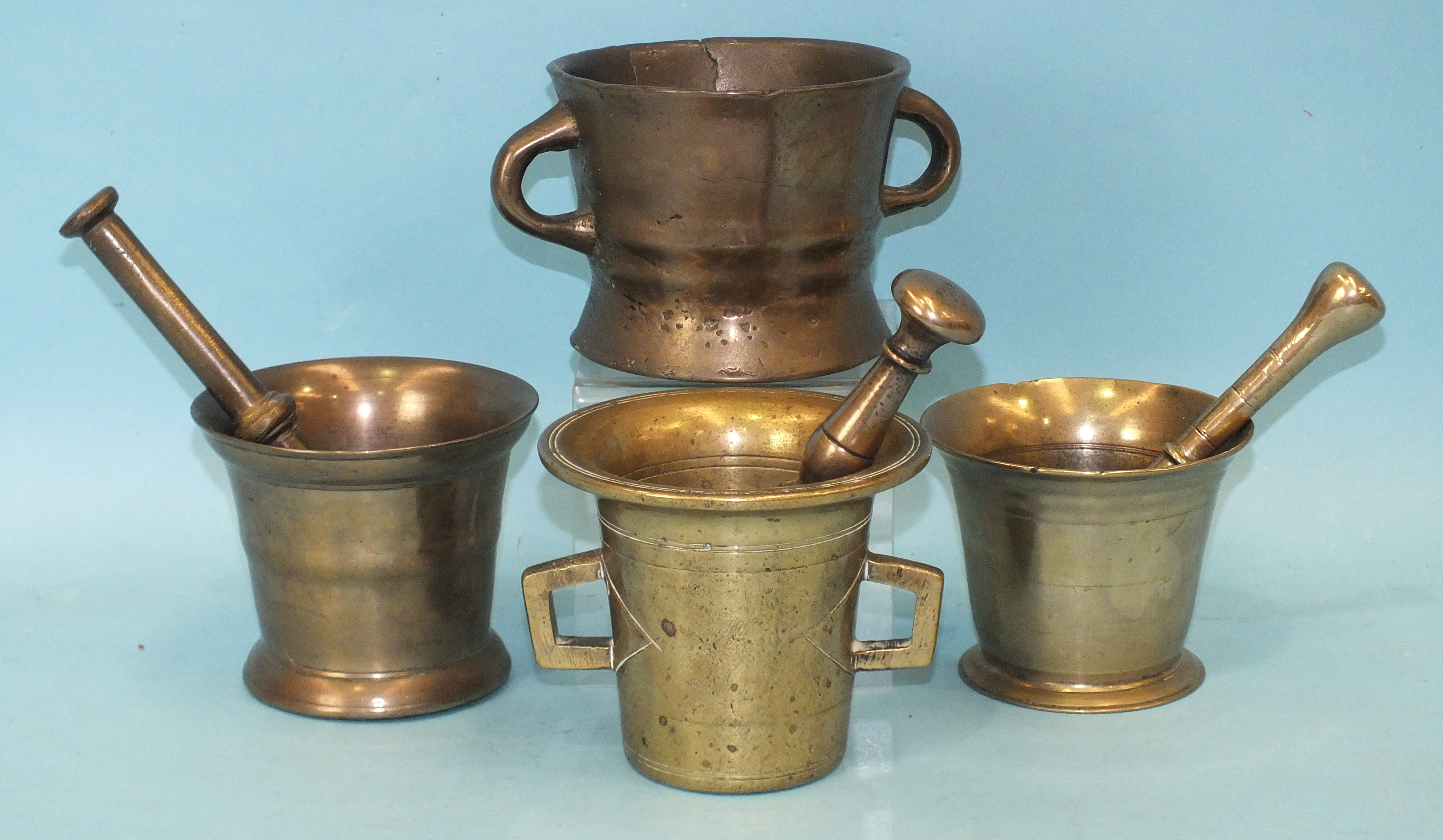 An antique bronze two-handled mortar, 10cm high, (a/f), together with three other bronze mortars and
