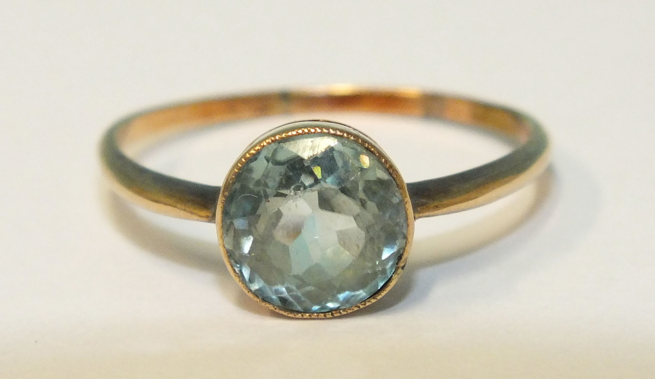 A gold ring set round-cut blue zircon, (wear to facet edges), in unmarked mount, (tests as 14ct