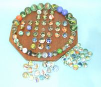 A wooden solitaire board with a selection of glass marbles, including fifteen hand-made marbles, (
