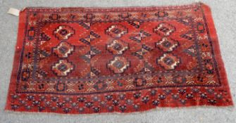 Persian red ground rug fragment, alternating stylised motifs within stylised floral borders,