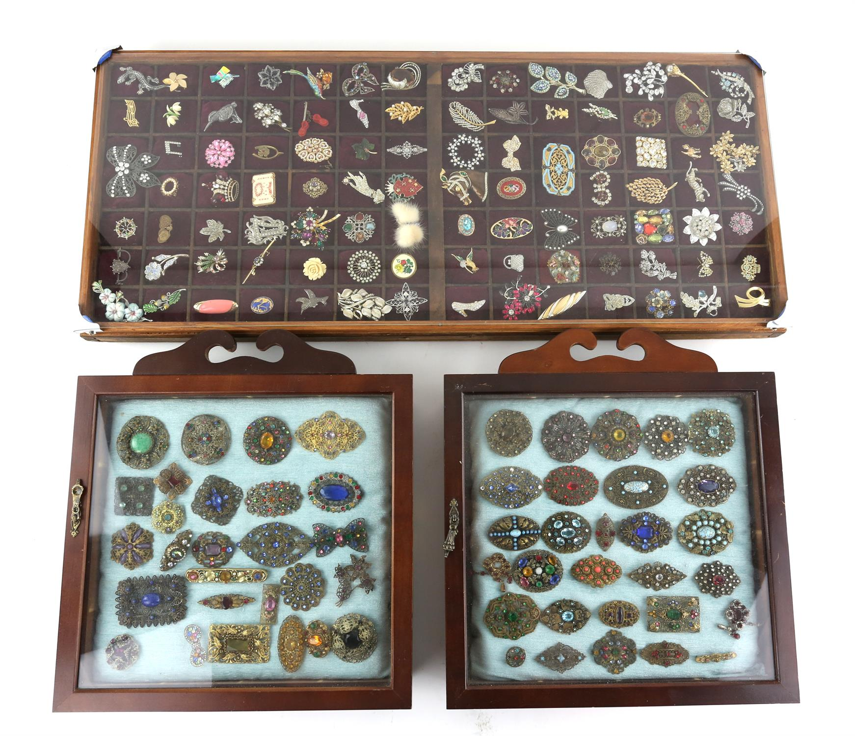 Three frames of brooches, largest frame measuring approximately 82 x 36.5cm, filled with colourful