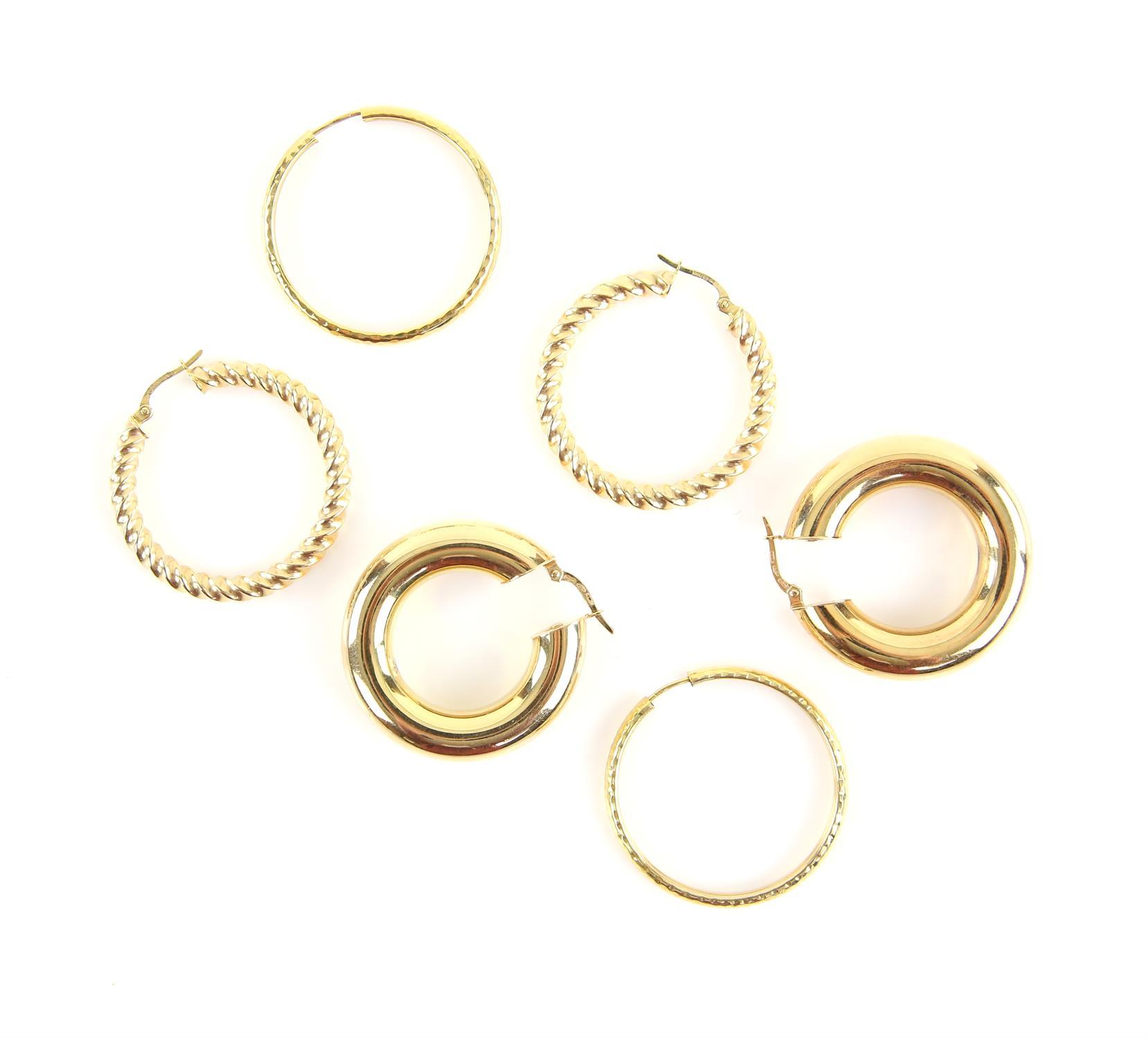 Three pairs of hoop earrings, including a pair of twisted gold hoops, measuring 3.