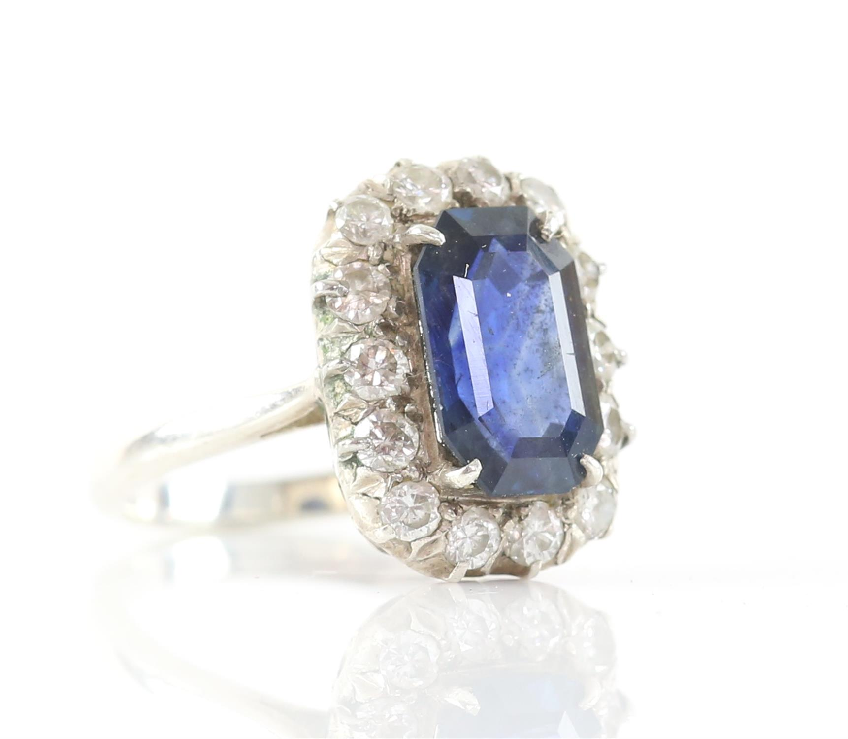 Sapphire and diamond cluster ring, with an emerald cut sapphire weighing an estimated 4.16 carats,