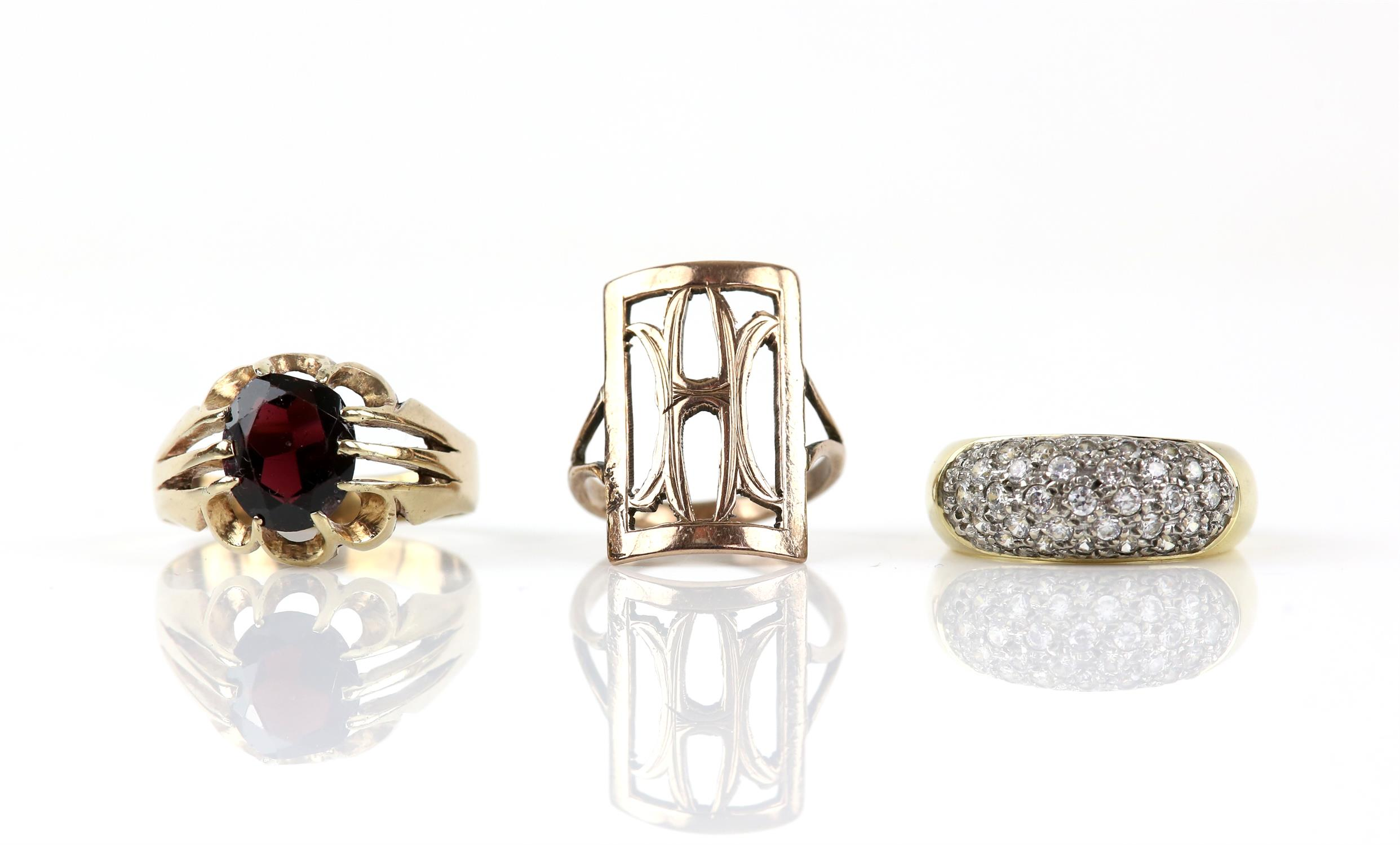 Three rings, including a single stone garnet ring, in 9 ct, ring size W, a multi stone cubic