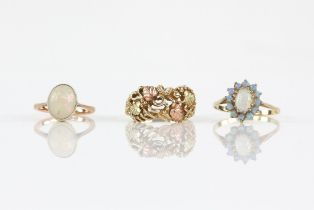 Three rings, comprising a single stone oval cabochon cut opal ring, opal 9 x 8 x 4mm,