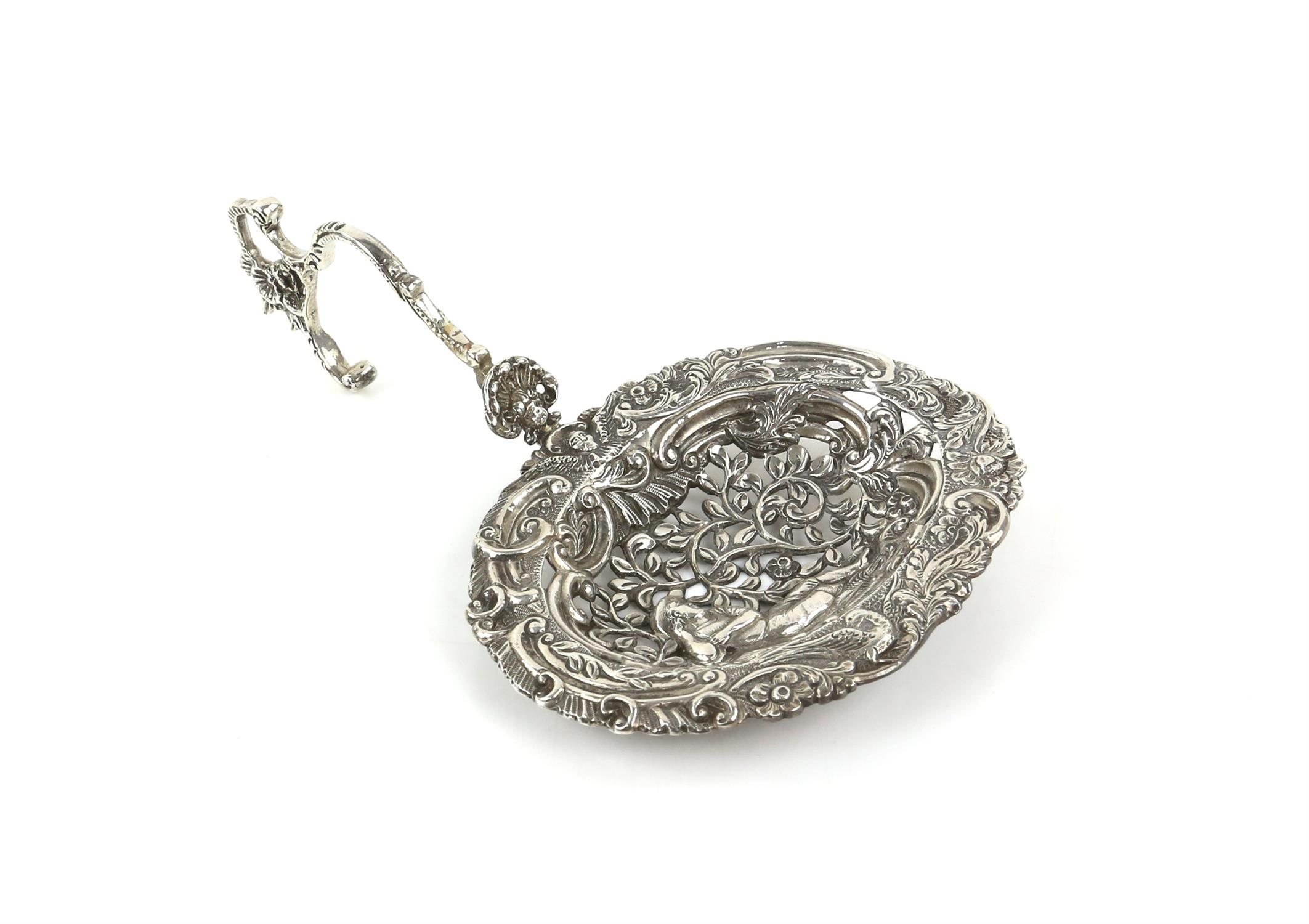 Large Continental silver bon bon sifter spoon with a man surrounded by foliage, import marks ETB