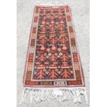 Afghan style war rug with label stating 'Ockenden Venture Pakistan - Produced by Afghan Refugees in
