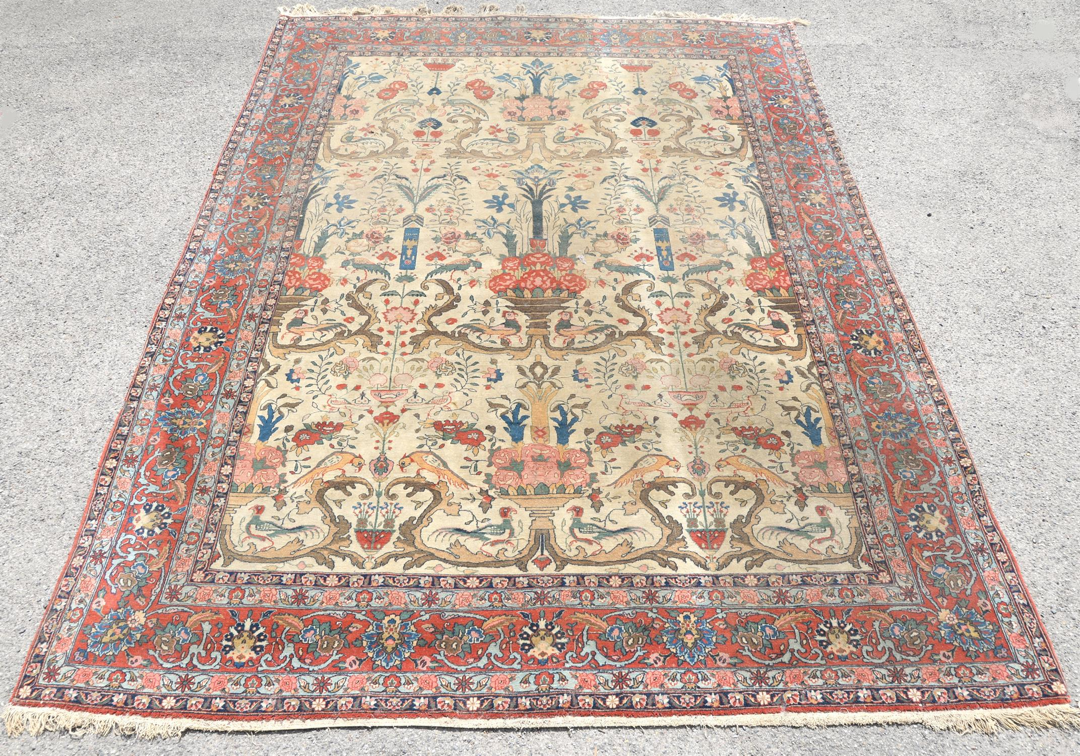 Persian carpet decorated with floral urns, birds and flowers within a floral border, 330 x 238cm