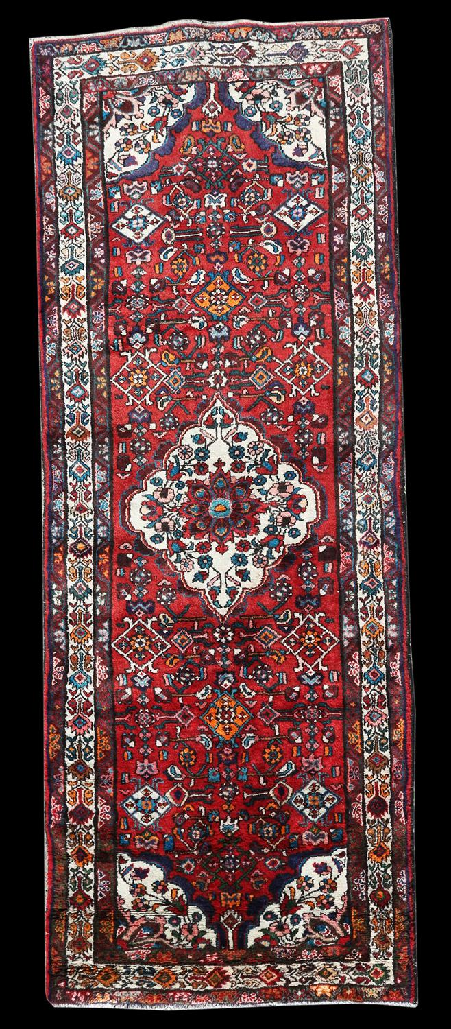 Persian village runner with floral medallion and floral motifs on a red ground, within floral - Image 3 of 4