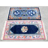 Chinese blue ground rug, central floral medallions and vases and furniture within a Greek key