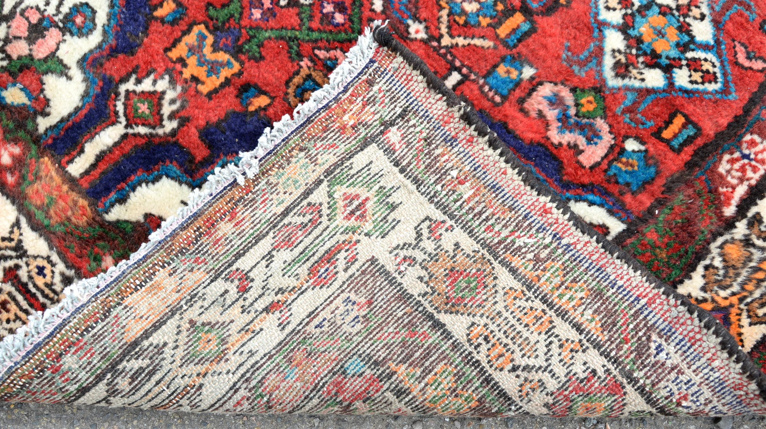 Persian village runner with floral medallion and floral motifs on a red ground, within floral - Image 2 of 4