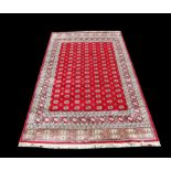 Bokhara style full pile carpet, Kashmir, with repeating Gul motifs on a red ground, 299 x 192cm