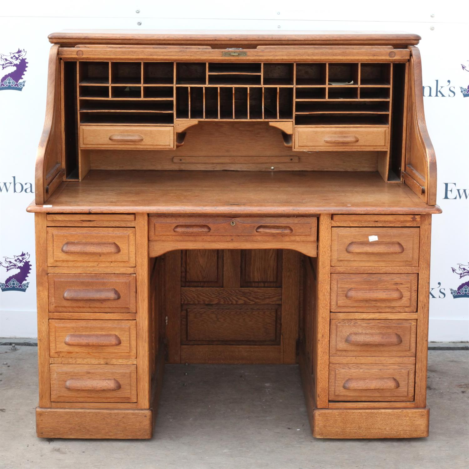 Early 20th century oak roll top desk, the roll top enclosing pigeon holes and drawers on base with