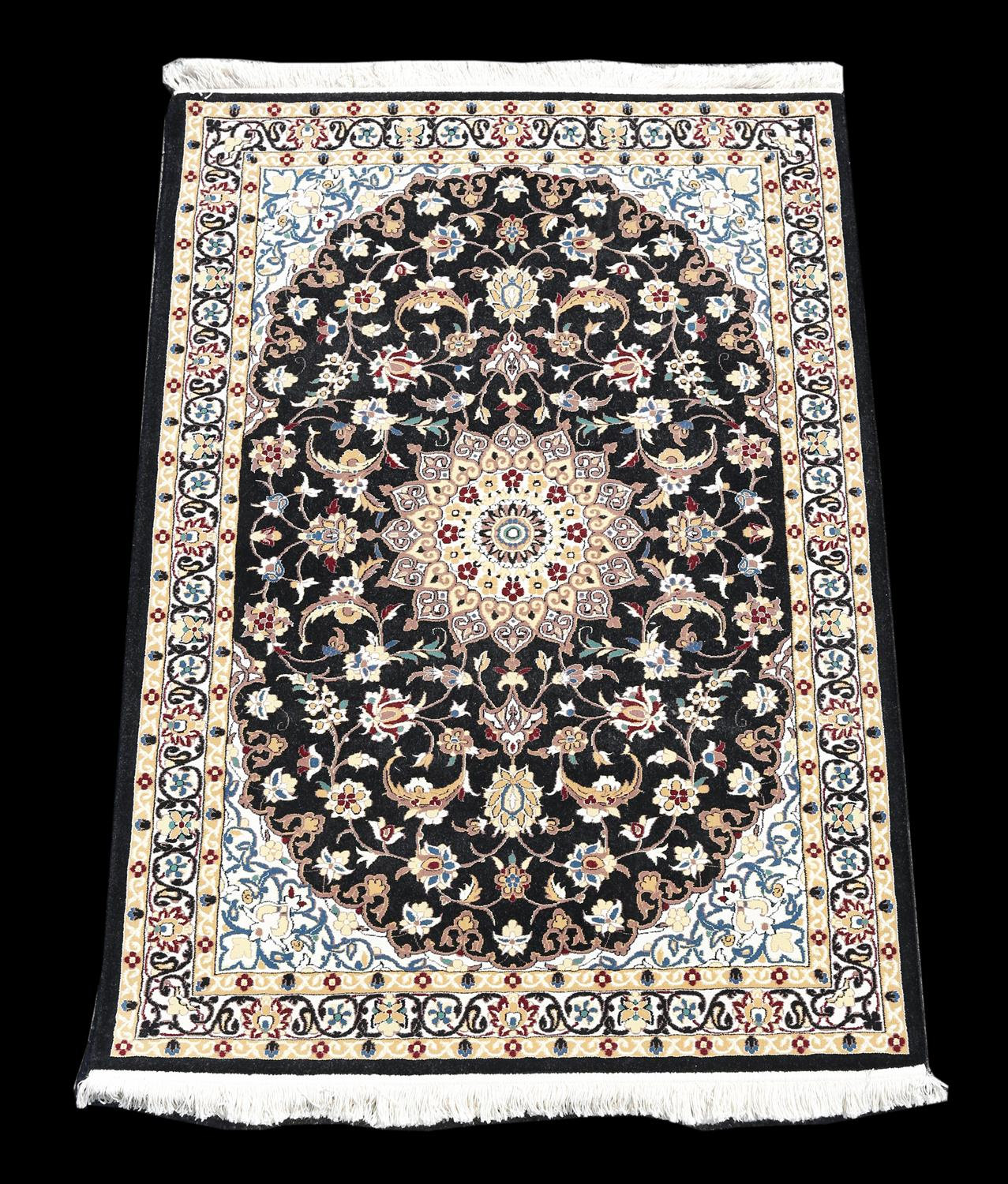 Persian style full pile rug, with central medallion and scrolling floral design on a black ground
