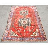 Persian Shiraz village carpet, with twin floral medallions on red ground with vine leaf and floral