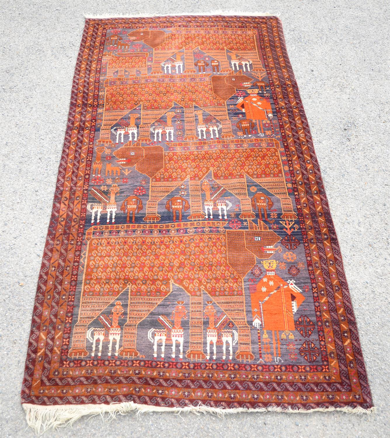 Pakistan rug in the Afghan style, decorated with camels, figures and boteh within floral borders,
