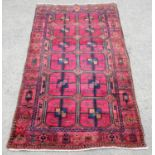 Burgundy ground Iranian village rug, with large Bokhara design with geometric motifs within