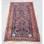 Pakistan rug in the Afghan style, having stylised motifs echoing the war in Afghanistan on a blue