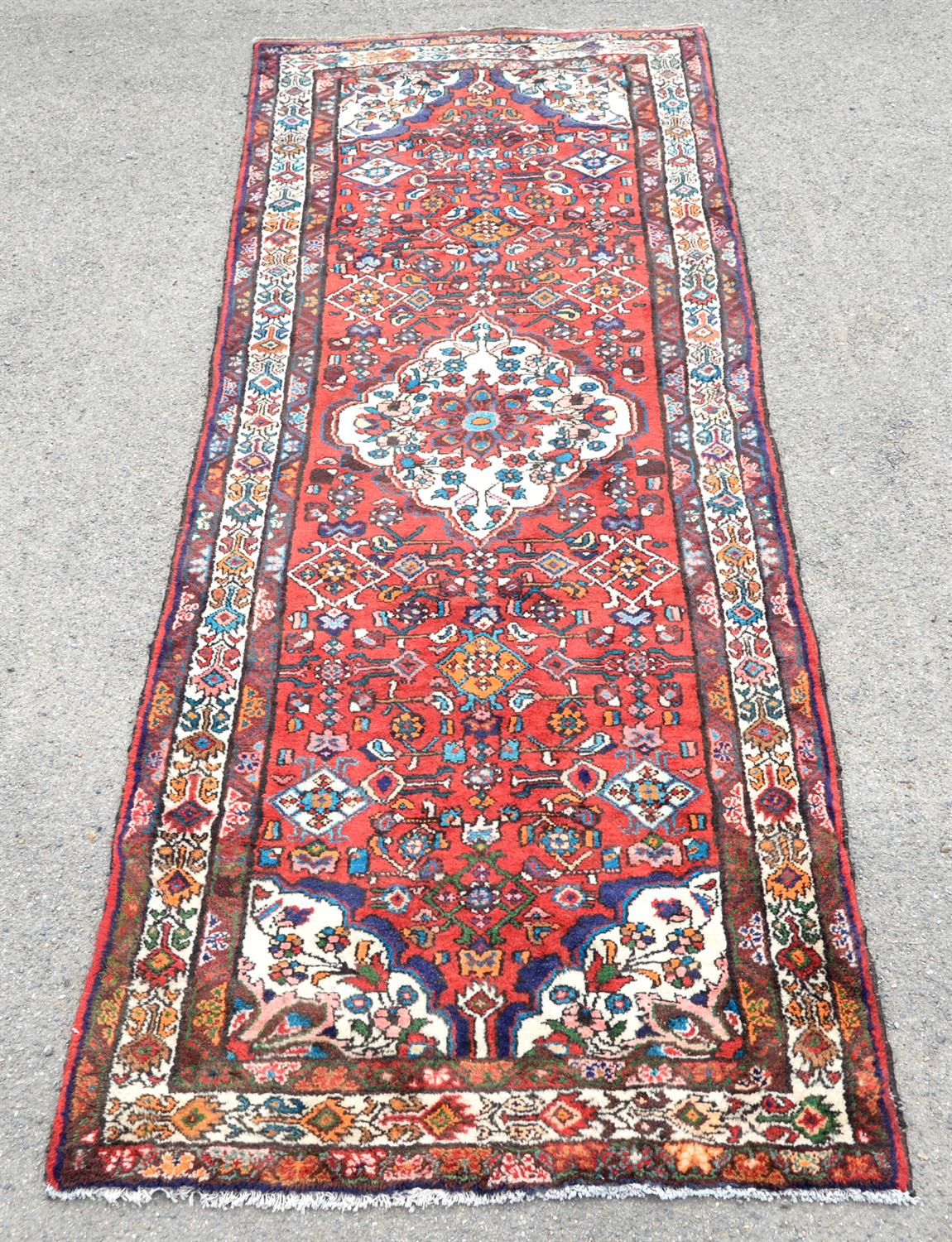Persian village runner with floral medallion and floral motifs on a red ground, within floral