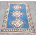 Turkish rug with three diamond medallions on blue ground within stylised floral border, 213 x 134cm