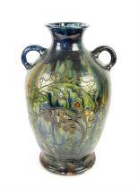 Large Burmantofts style twin handled glazed vase, decorated with fruit trees, 60cm high